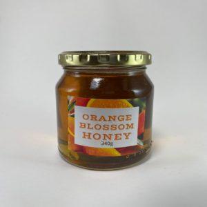 orange blossom raw honey 340g jar with a white background