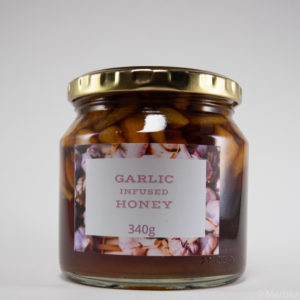 Garlic fermented raw honey in a glass jar with a white background